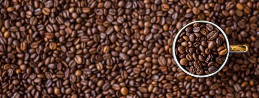 Cup of coffee beans sitting on a bed of whole coffee beans